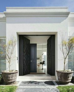 Contemporary entrance with classic references. Very pleasing looking through an open, double pair of black doors. Front doors heavily decorated with fretwork/close geometric moulding. Second pair, classical detailing. Lovely stepped 'cornice' (wrong word I think - can one of you kind architects tell me? I know you have these with a mansarde roof but not sure here) continues around the building to give harmony. The horizontal shutters bring surprise. Love it.