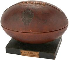 Knute Rockne & Pop Warner Signed Football Humidor. his unusual football-shaped humidor on dark wood base is actually made from a hollowed-out Spalding official collegiate football with the Spalding logo stamped into the leather. The stitching remains at the top of the ball, which has been cut in half laterally and opens on a hinge.  $6224