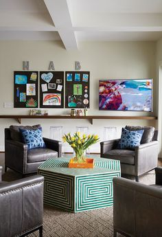 TV room and craft room combo features a gathering area boasting gray leather chairs with brass nailhead trim adorned with blue geometric pillows surrounding a green bone inlay concentric coffee table.