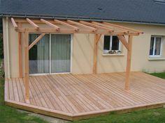 Terrasse fabriquée avec des lattes de bois sur laquelle une pergola très simple a été érigée. Cette dernière ne recouvre pas la totalité de la terrasse.