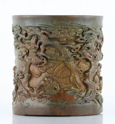 """Carved bamboo brush pot, China, carved in high relief with groups of figures under pine trees and other scenes of rural life, 5 3/4"""" x 5 1/2""""."""