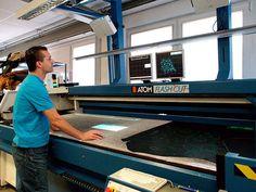 Der Materialzuschnitt erfolgt durch einen computergesteuerten Schneidetisch der seine Aufträge vollautomatisch aus einem Warenwirtschaftssystem bezieht und dem die benötigten Modelldaten (Schnittmuster) übergeben wurden.