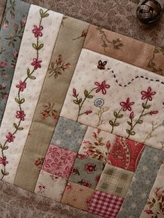 Embroidered flowers on patchwork quilt.