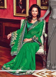 Green faux chiffon saree is design with fancy zari embroidered drop pattern motifs on both alternate sides and pallu. Sporadically spread stick on crystals and shimmer patch border agglomerates the lo...