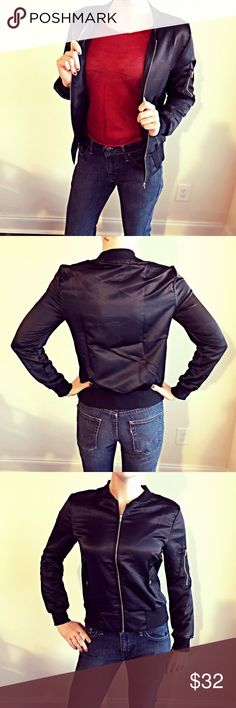 "Black Satin Bomber Lightweight black satin bomber jacket. Perfect for chilly seasons!! Wears like a shirt in terms of how thin it is (I love to wear mine indoors for the jacket look, without the heat of wearing a heavy one). Gold accents and faux pockets.                                                  I'm 5'7 120lbs and wearing a Medium. Approximately...                                                           Bust- 39.4"" M and 40.9"" L.                                              Length…"