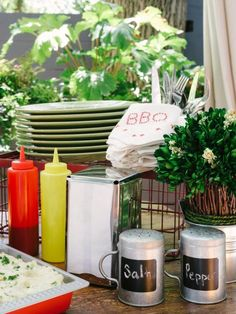 Since guests will be lining up to serve themselves, dedicate one end of your buffet table to making plates, linens and condiments easily accessible. Stack plates up casually, keeping them elevated with risers. Transfer ketchup and mustard from their containers into restaurant condiment bottles for a more personal touch.