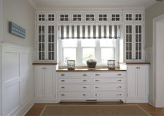 Butlers pantry with white cabinets with glass fronts, a striped roll up shade, wood floor and wall panel molding