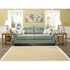 Gently curving arms and button-tufted back cushions give this fashionable sofa a contemporary look.  Upholstered in stylish lagoon-green with complementing floral-print throw pillows, this fabulous Kylee sofa will enliven any modern setting.