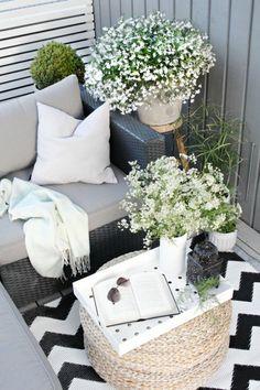aménagement-balcon-fauteuil-coussins-décoratifs-gris-table-ronde-en-paille-plante-verte
