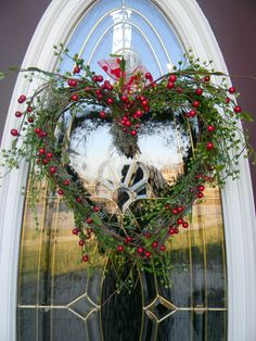 Heart wreath with red berries, perfect for wintery February and Valentines.... A heart shaped grapevine wreath filled with bright green mini lotus foliage, red berry branches, and spanish moss.