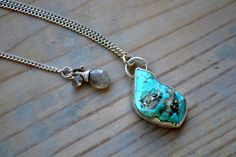 abstract shaped turquoise with sparkling pyrite accents, enveloped in hand forged silver bezel. strong sterling silver s-chain. adjustable length -