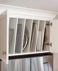 Over the refrigerator cabinet lid,pan and cookie sheet organization with slanted wooden dividers.