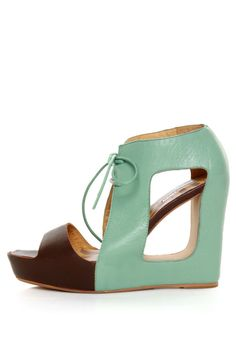 """As Seen On Julie of Orchid Grey Blog!! With architectural cutouts, cool color blocking, and sassy laces, the Matiko Paris Light Blue & Brown Lace-Up Cutout Wedges more than live up to their namesake! Minty sea green leather upper has an amazing cutout at the arch, plus coated shoestrings to tie around the ankle, with a brown leather toe band for some gorgeous color blocking appeal. Hidden brown platform builds from 1"""" at toe, to 4.5"""" at the wedge heel (plus rubber tip), with a s..."""