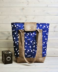Stunning large tote bag in a navy swallow print with complementary brown recycled leather and pretty black and white flowery lining.