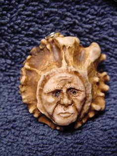 Hand carved antler shaman face on antler button pendant.  via Etsy.