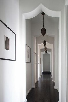 A long Mediterranean hallway boasts a wall lined with a sepia toned photo gallery as well as Moorish style doorways illuminated by pierced metal Moroccan lanterns.