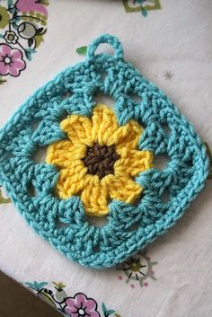 It's a classic solid color granny square with a simple black eyed susan flower in the center. Use other colors and you will have asters or daisies or fantasy flowers. Very easy :)