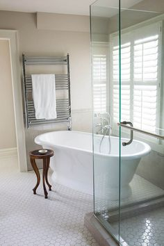 Free standing tub on an angle and glass corner shower with hex tile floor. R. Cartwright Design - Des Moines Iowa Interior Designer