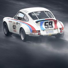 Vintage Porsche in racing livery out on the track.