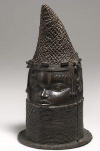 Cabeça da iyoba, a rainha-mãe de Benin. Os rostos são individualizados assim como os adornos. As escoriações na testa e acima das sobrancelhas são marcas identitárias da cultura edo e da linhagem real. Bronze, 42,5 cm de altura, 1750-1800, Edo/reino de Benin, Nigéria.