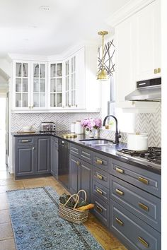 stunning kitchen features white upper cabinets and gray lower cabinets adorned with brass hardware paired with black quartz countertops and white a