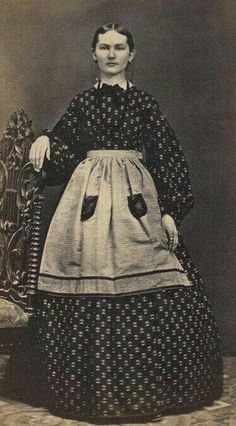 This is a woman showing off her apron that was worn at special events - such as entertaining guests in the parlor.