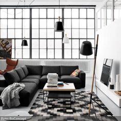 Eine Einrichtung in Schwarz-Weiß bekommt durch gezielt gesetzte Highlights mehr Spannung. Die Pendelleuchten variieren in ihrer Höhe, der Teppich wirkt aufgrund seines Musters in unterschiedlichen Farbnuancen dreidimensional. Bunte Sofakissen lockern das Gesamtbild auf.