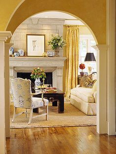 Country French from bhg.com Arching Views Pleasant arches offer views of adjoining rooms in this home. Golden walls combine gently with neutral flooring and mantel, accented only with a bit of black and touches of blue-and-white porcelains. Softly puddled draperies have a luxurious yet casual feel.