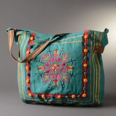 Turquoise embroidered bag - National Cowboy Museum Bright, sunny turquoise embroidered center front with sequins accent. Three-way ribbons and rick-rak with pompoms sewn down striped border.