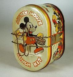 boxes, America, A lithographed tin Mickey Mouse Lunch Kit by Handy, 1935, having an oval form with pie tray and folding handles.