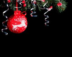 Red knitted Christmas ball. Black background