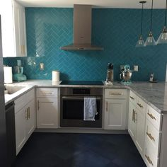 Amazing kitchen!  Teal herringbone backsplash, white cabinets, grey counter and charcoal floors!
