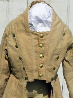 young boy's frock coat is simply fabulous. Unlined and fashioned out of a finely hand-woven, hand-dyed bittersweet cotton, rural Pennsylvania frock coat is hand-sewn. excellent condition, retains all but one of its 16 original steel shank brass buttons with hand-hammered design. in addition to being used for closure, they decorate the sides of the lapels as well as punctuating the waist in the back. It even retains its original hand-woven tape at the nape of the collar used for hanging.