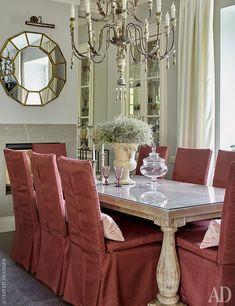 Столовую и гостиную разделяет двусторонний камин. Справа от него — стеклянная стена и встроенный сервант. Зеркало, Gramercy Home.