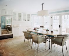 Love the pendant over the table, good way to delineate dining space. June July 2012 Issue Photo - Woven chairs and a marble table in a breakfast nook
