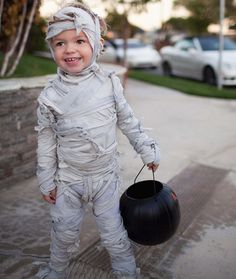Make an easy Halloween costume with a bed sheet that screams MUMMY.