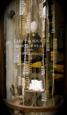 John Smedley, Brook St, London UK. Wash-day themed care products window. Vintage factory chair, 35m sisal rope and 1200 wooden pegs. Also displayed are the original ceramic moulds for household rubber gloves