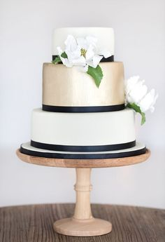 black and white wedding cake with brushed gold gum-paste magnolia and navy ribbon