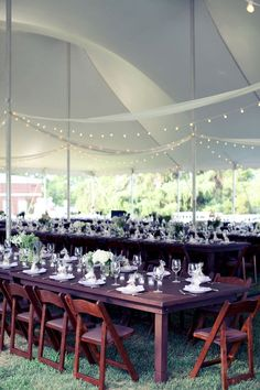 white pole tent with string lights and wooden tables