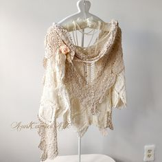 This is a layered crochet shawl. The basic piece is an eggshell color open, lacy crochet.  Then I added two pieces for the neck: the first one