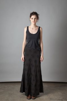 """100% organic medium-weight cotton jersey Long Skirt with negative reverse appliqué in our Large Polka Dots pattern. Fitted at waist with generous flare to hem and a slight train in back. Measures 41"""" at center front and 45"""" at center back. Shown here in Black. Choose your color below.Please allow four to six weeks for delivery. Wash gently + Hang to dry. Free shipping. Made in the USA."""