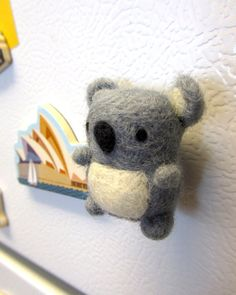 ~Made to Order~  Go down under by adding this charming needle felted koala magnet to your fridge. The koala is handmade with love out of 100% natural wool. This miniature koala friend would make a perfect gift for an animal lover or anyone who enjoys cute things.  Measurements are approximately:  3.5cm w x 4.0cm h (1.4w x 1.5h)  As this item is made to order, it may vary slightly from the photos shown. Each is handmade and one-of-a-kind.  Item will be carefully packaged using recyclable…
