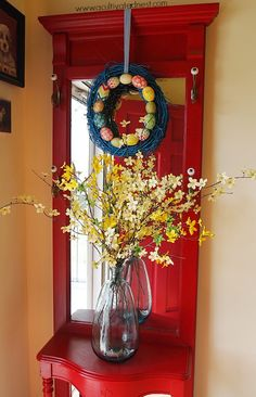 I glued a few fake Easter eggs onto a grapevine wreath that I already had I spray painted it blue.  I also took some fake forsythia branches and placed them in a blue glass vase