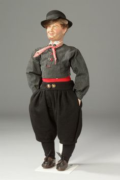 Klederdrachtpop van een man uit Marken, 1900-1949 De man is gekleed in de daagse dracht, een wit linnen hemd met beffie en twee zilveren halsknopen, daar boven de gezondheid en een zwart-witte boezeroen, een rood geruit dookie om de nek geknoopt, de zwart wollen bovenbroek met twee donkere knopen met ivoren kern, daaronder zwart wollen kousen en leren schoenen met veter, de pop is van keramiek en heeft echt haar. #NoordHolland #Marken