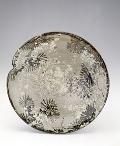 JServing dish  early 19th century    Kiyomizu Rokubei II , (Japanese, 1777-1847)   Edo period     Stoneware with white slip and iron pigment under feldspathic glaze  H: 6.3 W: 27.7 cm   Kyoto, Japan.  This large plate borrows its decor from a bowl by the early 18th-century potter Ogata Kenzan. Pine boughs are rendered in broad strokes of underglaze iron, while white slip spattered over the surface becomes drifting snow.