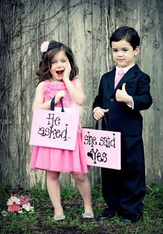 Kids close up with sign that says and they lived happily ever after and bride and groom in the back groom kissing (beach setting )