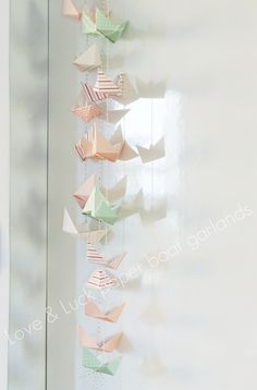 how perfect would this be in our nautical living room with vintage maps?  Love & Luck paper boat garland