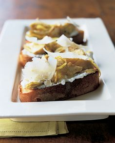 Artichoke hearts with ricotta and Parmesan cheese on hearty slices of rustic bread adds up to a tangy appetizer or finger food that's easy to make.