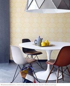 Behangcollectie Impulse _ met een donkere vloer, bruine bank en gele gordijnen.