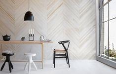 La madera como pared y la variante de sillas, se destacan en los tonos neutros elegidos para este espacio